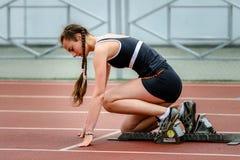 Menina pronta para começar correr na pista de atletismo Fotografia de Stock Royalty Free