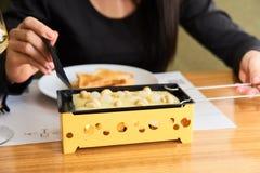 A menina prova o raclette do queijo em um café Imagens de Stock Royalty Free