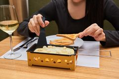 A menina prova o raclette do queijo em um café Foto de Stock
