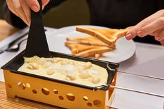 A menina prova o raclette do queijo em um café Imagem de Stock