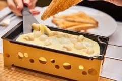 A menina prova o raclette do queijo em um café Fotografia de Stock Royalty Free
