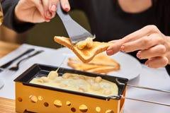 A menina prova o raclette do queijo em um café Imagens de Stock