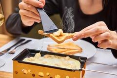 A menina prova o raclette do queijo em um café Delicioso e com vapor quente Foto de Stock