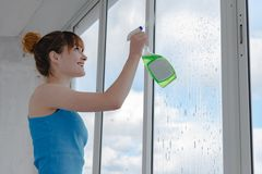 A menina pulveriza o líquido para janelas de lavagem no vidro sujo imagem de stock