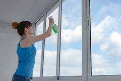A menina pulveriza o líquido para janelas de lavagem no vidro sujo foto de stock royalty free