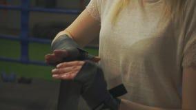 A menina puxa uma atadura de encaixotamento em sua mão closeup video estoque