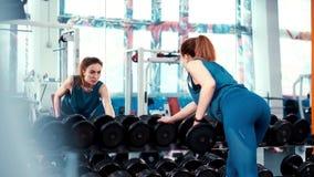A menina quadro-nova larga da aptidão executa um exercício com um peso na frente de um espelho enorme vídeos de arquivo