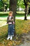 Menina que é inclinação virada contra a árvore imagens de stock royalty free