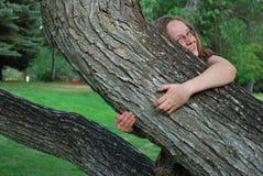 Menina que abraça a árvore Fotografia de Stock