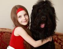 Menina que abraça um cão imagem de stock