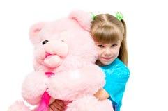 Menina que abraça um urso cor-de-rosa Fotografia de Stock