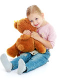 Menina que abraça um urso de peluche Imagem de Stock