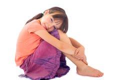 Menina que abraça joelhos à caixa Foto de Stock