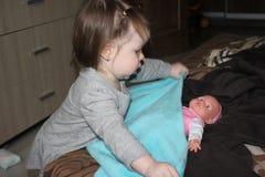 Menina que abriga com cuidado uma boneca Imagens de Stock Royalty Free