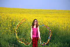 Menina que acena com as fitas coloridas na mola s do campo Foto de Stock