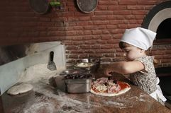 Menina que adiciona azeitonas pretas à pizza Foto de Stock Royalty Free