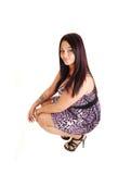 Menina que agacha-se no assoalho. Imagens de Stock