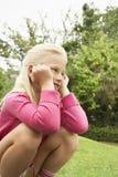 Menina que agacha-se no parque Fotos de Stock