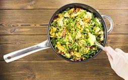 Menina que agita vegetais cozidos em uma frigideira, fundo de madeira, close-up, vegetais imagem de stock royalty free