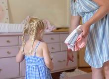 A menina que ajuda a mamã grávida pôs a lavanderia limpa no dresse foto de stock
