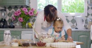 Menina que ajuda seu Mum com o cozimento video estoque
