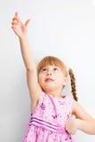 Menina que alcanga para algo com suas mãos. Imagens de Stock Royalty Free