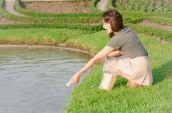 Menina que alimenta para peixes Fotografia de Stock