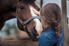 Menina que alimenta seu cavalo Fotografia de Stock Royalty Free