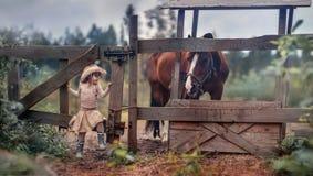Menina que alimenta seu cavalo Imagens de Stock
