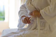 Menina que amarra seu bathrobe branco Fotografia de Stock Royalty Free