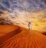 Menina que anda abaixo da duna de areia Fotos de Stock Royalty Free