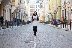 Menina que anda abaixo da rua com seu telefone Fotografia de Stock