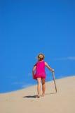 Menina que anda acima da duna de areia Fotografia de Stock