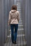 Menina que anda afastado através do corredor cinzento Imagem de Stock