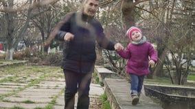 Menina que anda ao longo do parapeito junto com seu avô no parque da cidade e que olha ao redor e que sorri na câmera filme