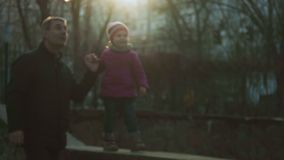 Menina que anda ao longo do parapeito junto com seu avô no parque e na vista ao redor e no sorriso da cidade childish video estoque