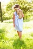 Menina que anda através do urso carreg da peluche do campo Foto de Stock Royalty Free