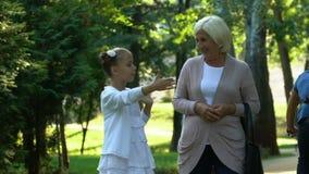 Menina que anda com avó e que diz suas histórias da vida da escola, confiança video estoque
