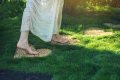Menina que anda com os pés descalços nas pedras na forma do coração Fotografia de Stock Royalty Free