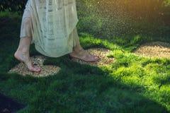 Menina que anda com os pés descalços nas pedras na forma do coração Fotografia de Stock