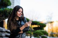Menina que anda e que texting no telefone esperto na rua que veste um casaco de cabedal no verão imagem de stock royalty free