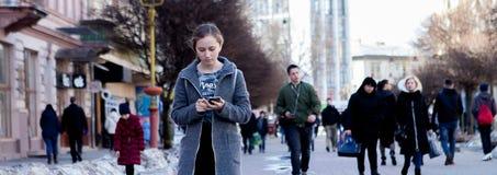 Menina que anda e que texting no telefone esperto na rua que veste um revestimento cinzento, no inverno imagens de stock