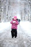 Menina que anda em um parque do inverno na neve Imagem de Stock Royalty Free