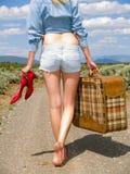 Menina que anda em uma estrada de terra com uma mala de viagem Fotografia de Stock Royalty Free
