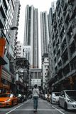 Menina que anda entre construções residenciais altas e carros caros em Hong Kong China imagem de stock