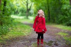 Menina que anda na chuva Imagens de Stock Royalty Free
