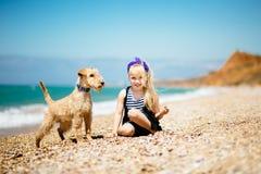 Menina que anda na praia com um terrier do cachorrinho fotos de stock royalty free