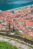 Menina que anda nas etapas rochosos à fortaleza de Kotor imagem de stock royalty free