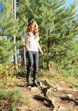 Menina que anda para baixo na floresta Foto de Stock
