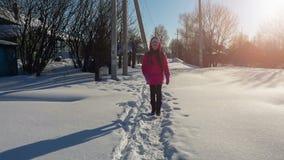 Menina que anda para dirigir da escola no dia ensolarado gelado, vídeo do hd do movimento lento vídeos de arquivo